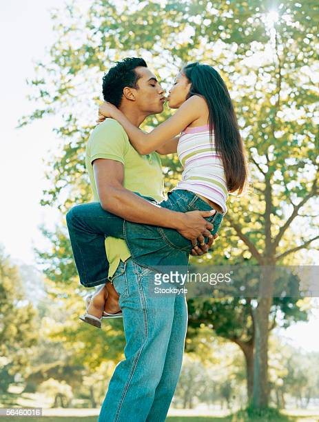 low angle view of a young man kissing a young woman - bacio sulla bocca foto e immagini stock
