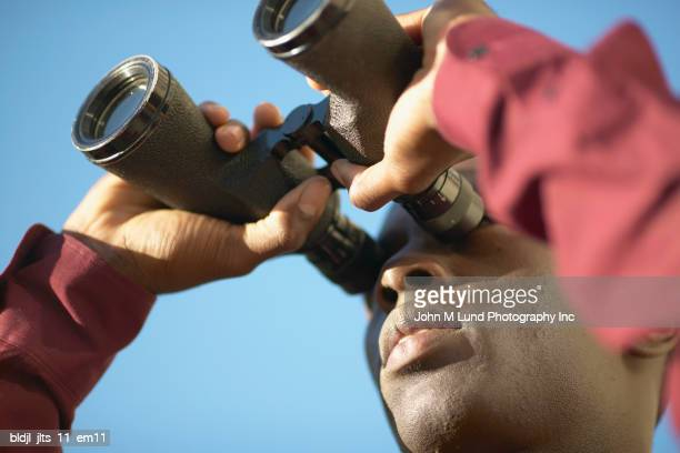 Low angle view of a young man looking through binoculars