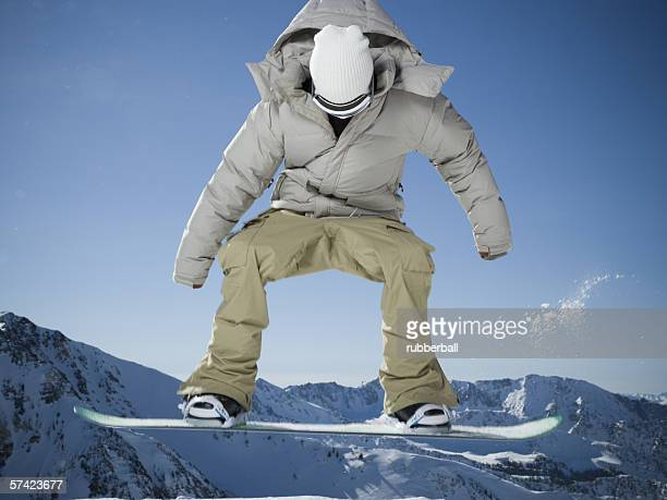 low angle view of a young man performing a stunt on a snowboard - ski pants stock pictures, royalty-free photos & images