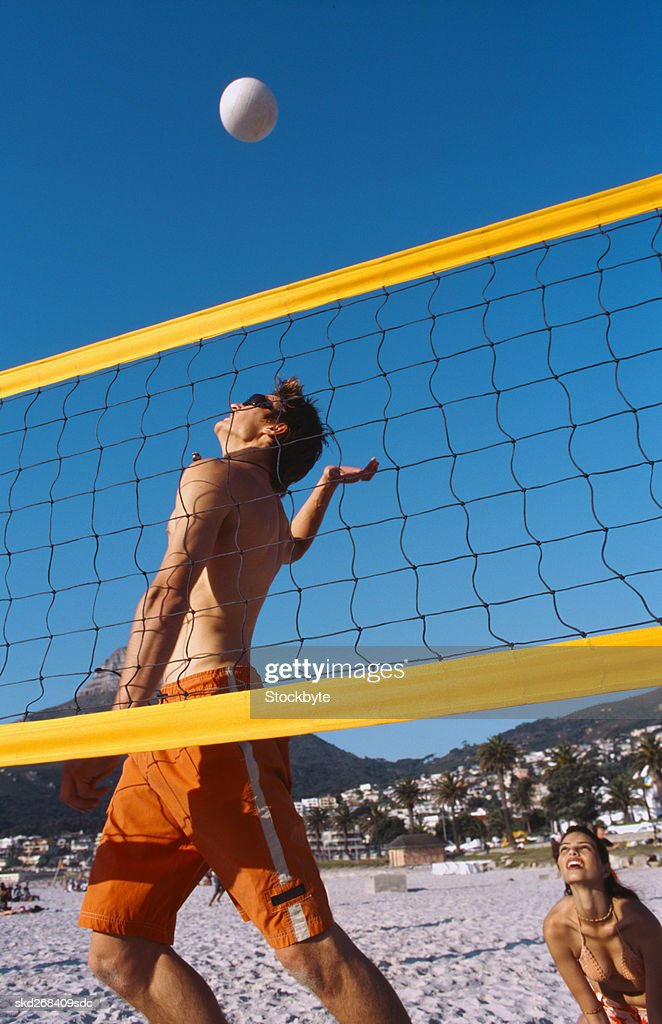 Low Angle View Of A Young Man Playing Volleyball On The Beach Stock Photo