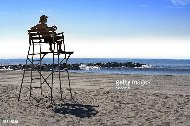 Low angle view of a young man sitting on a lifeguard chair