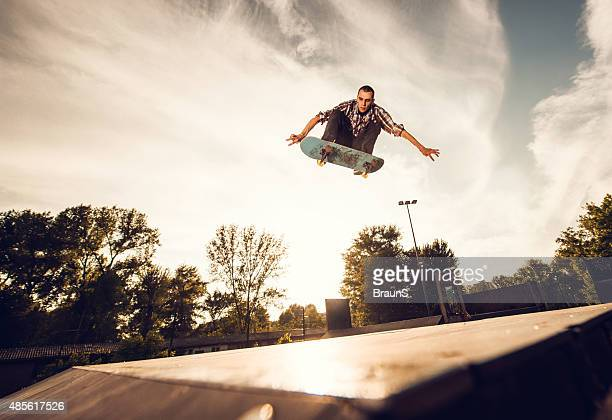 Low angle view of a young man skateboarding at sunset.