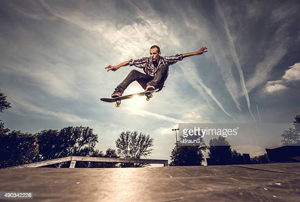 low angle view of a young man skateboarding outdoors. - skating stock photos and pictures