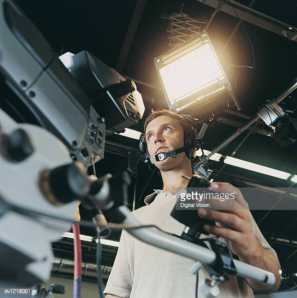 Low Angle View of a Young Man Using a TV Camera in a TV Studio