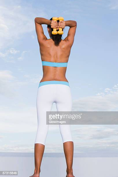 low angle view of a young woman exercising with dumbbells - seulement des adultes photos et images de collection