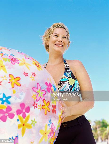 low angle view of a young woman holding a beach ball - fat woman at beach stock pictures, royalty-free photos & images