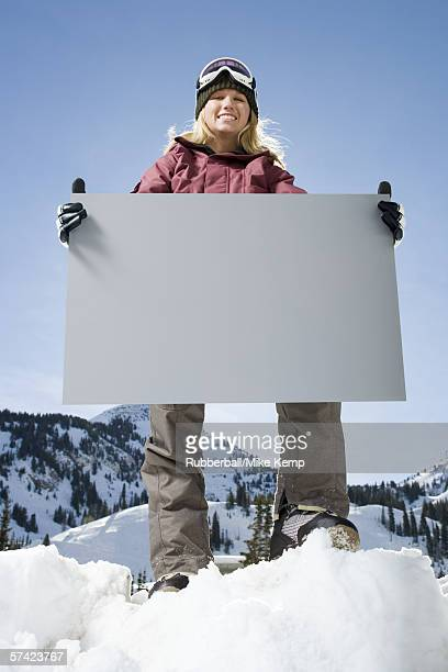 low angle view of a young woman holding a blank sign - ski wear stock pictures, royalty-free photos & images