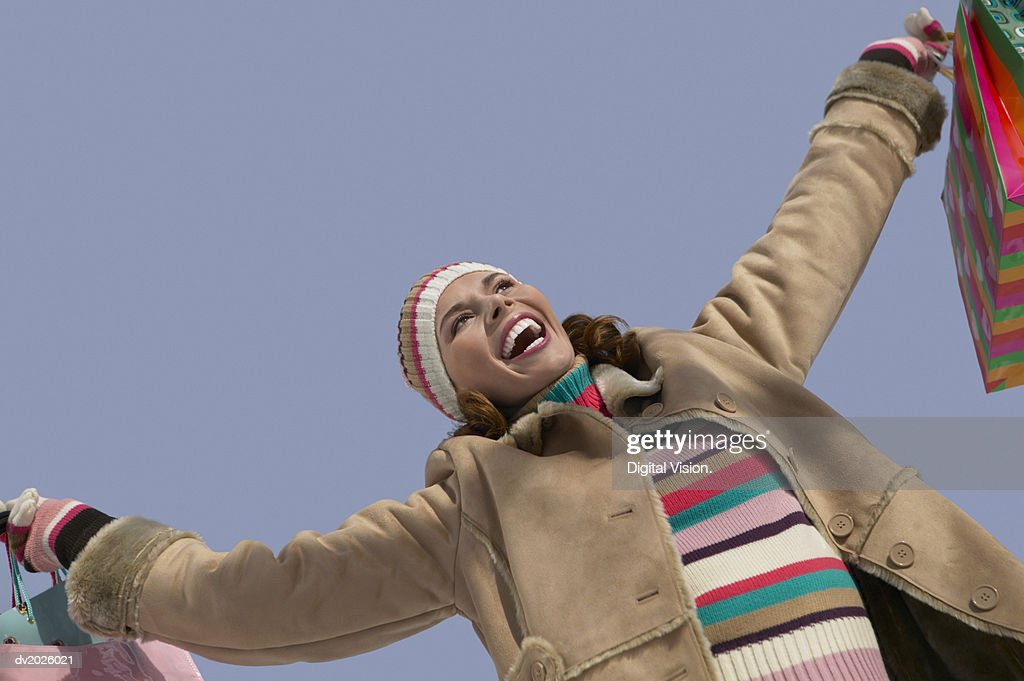 Low Angle View of a Young Woman in Winter Clothing Holding Out Shopping Bags and Cheering : Stock Photo
