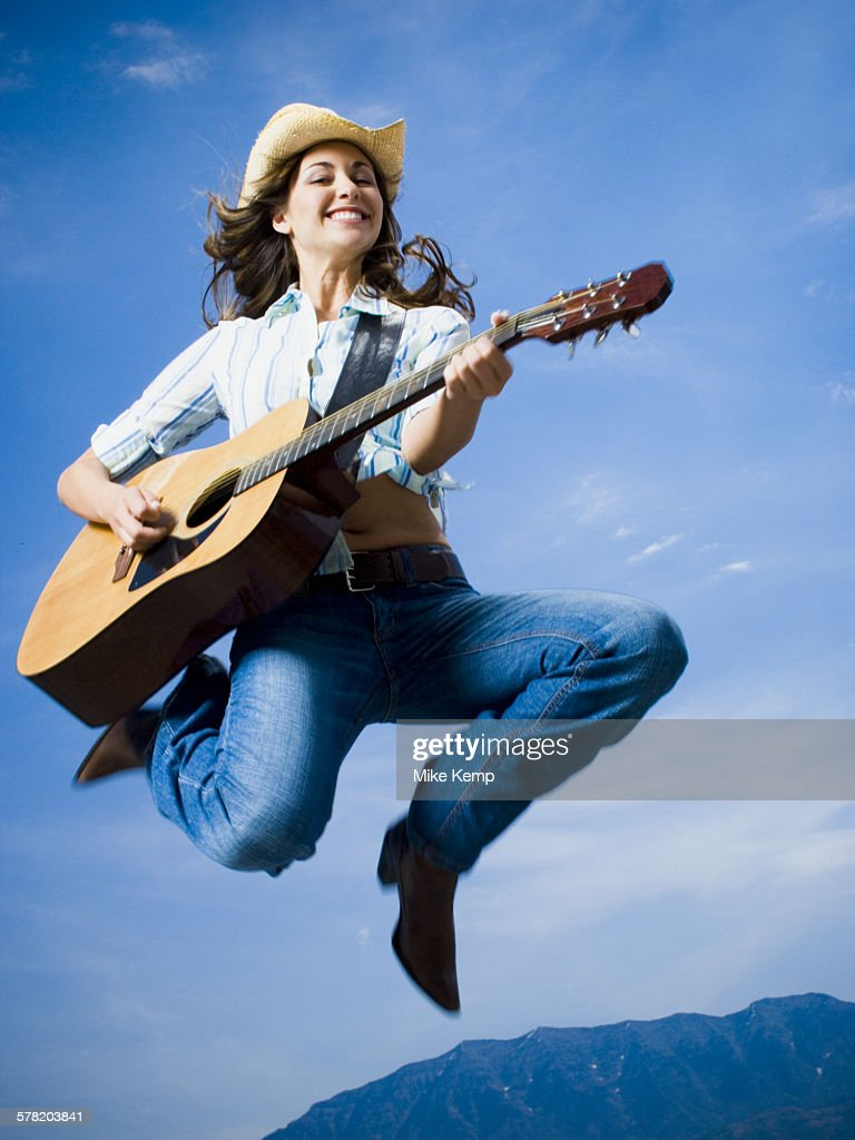 Low angle view of a young woman jumping and playing the guitar : Stock Photo