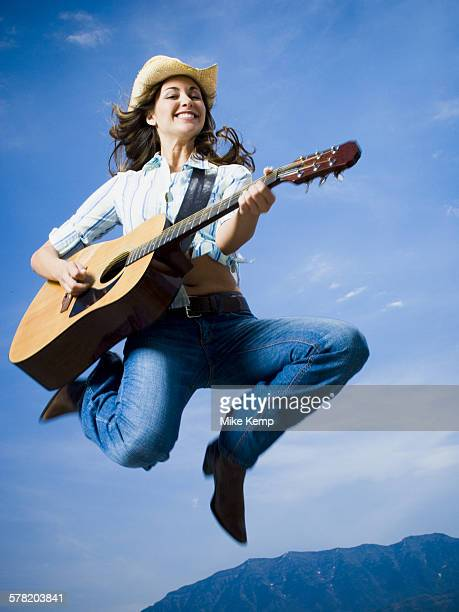 Low angle view of a young woman jumping and playing the guitar