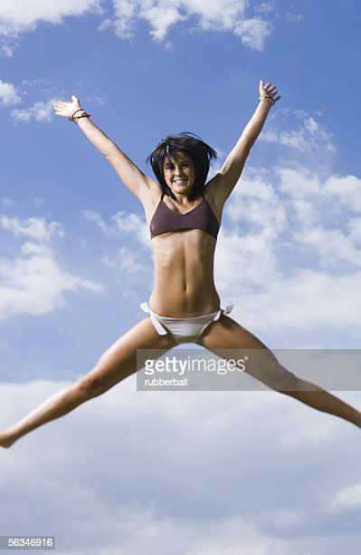 low angle view of a young woman jumping - legs apart stock photos and pictures