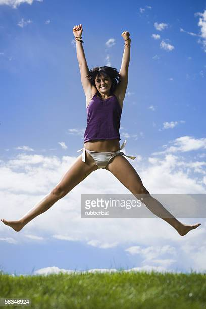 low angle view of a young woman jumping - legs spread woman stock photos and pictures