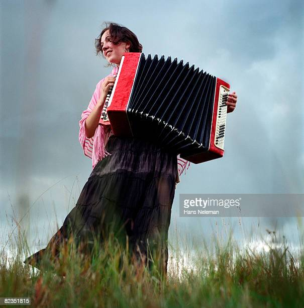 Low angle view of a young woman playing an accordion, Russia