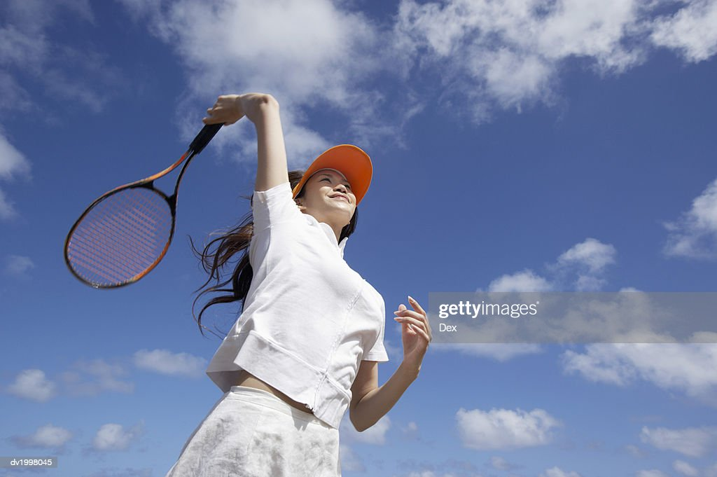 Low Angle View of a Young Woman Playing Tennis : Stock Photo