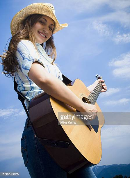 Low angle view of a young woman playing the guitar