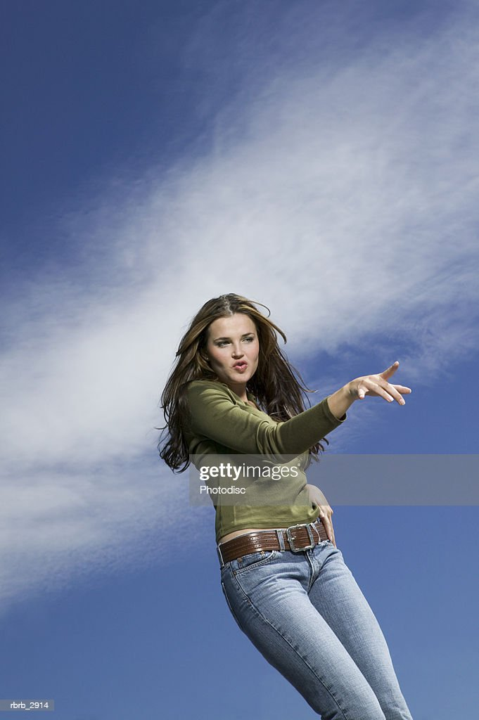 Low angle view of a young woman pointing : Foto de stock