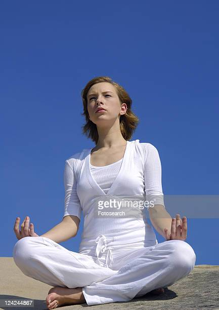 Low angle view of a young woman practicing yoga in the lotus position