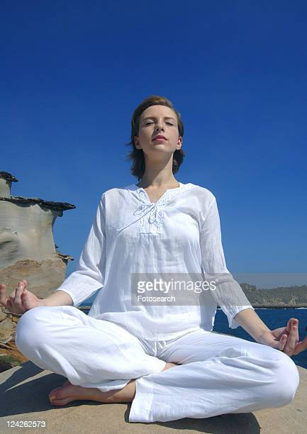Low angle view of a young woman practicing yoga