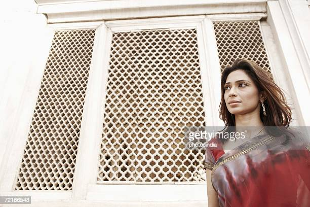 Low angle view of a young woman standing in front of a window