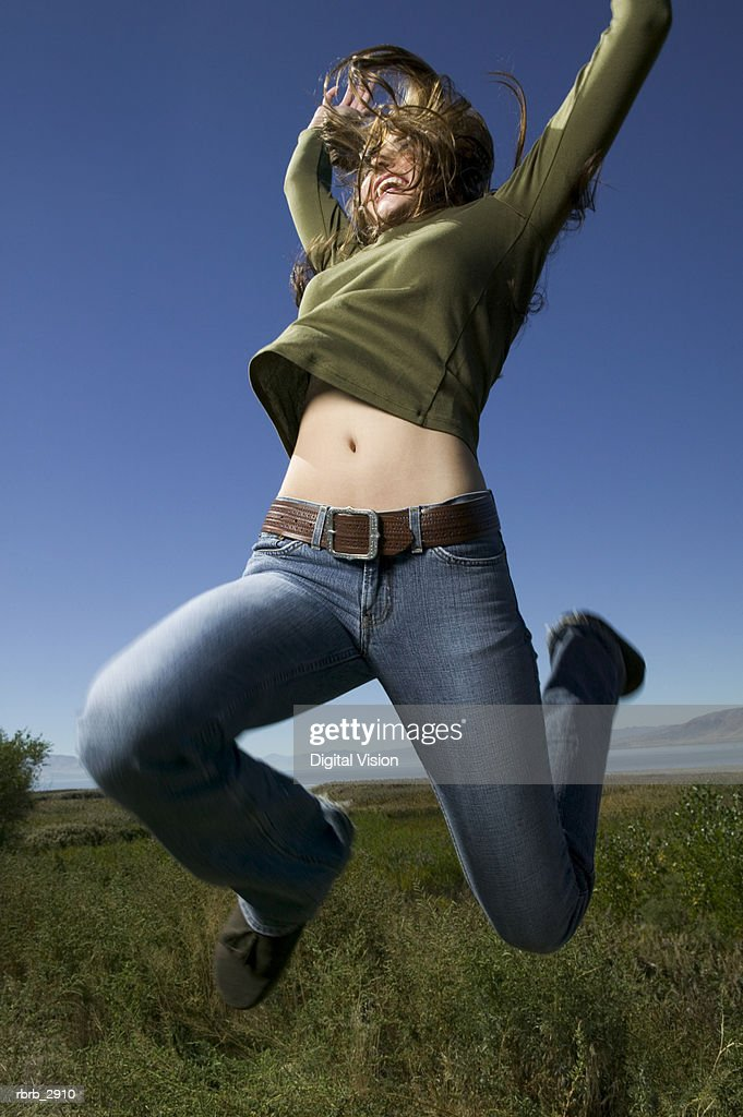 Low angle view of a young woman standing on a grassy field with her arms raised : Foto de stock