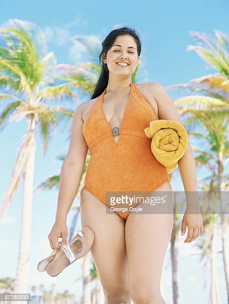 low angle view of a young woman standing on the beach, holding a towel and flip-flops - fat woman at beach stock photos and pictures