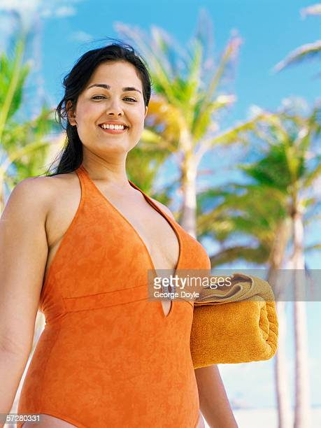low angle view of a young woman standing on the beach - dicke frauen am strand stock-fotos und bilder