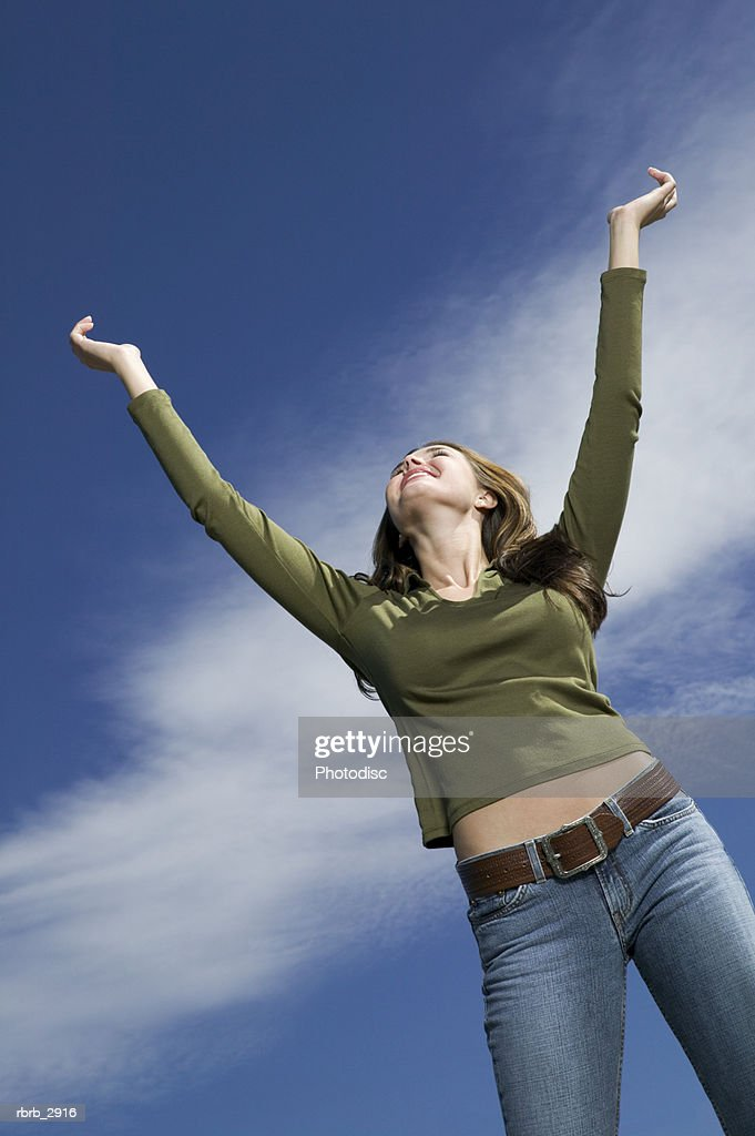 Low angle view of a young woman standing with her arms raised : Stockfoto
