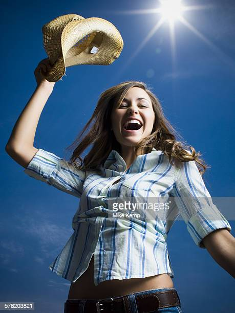 low angle view of a young woman with her arms raised - vitalität stockfoto's en -beelden