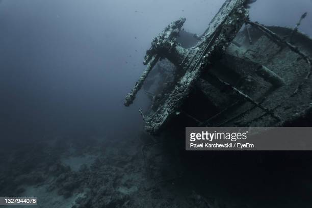 low angle view of abandoned boat on sea - underwater film camera stock pictures, royalty-free photos & images