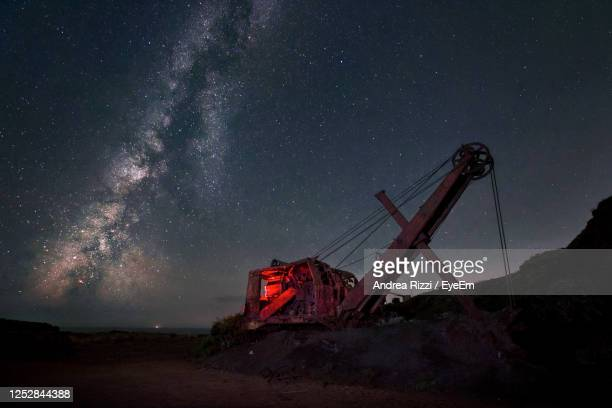 low angle view of abandoned crane against sky at night - andrea rizzi foto e immagini stock