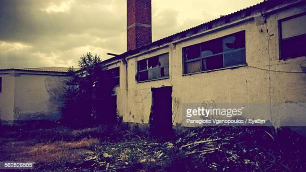 low angle view of abandoned factory against cloudy sky - vgenopoulos stock pictures, royalty-free photos & images