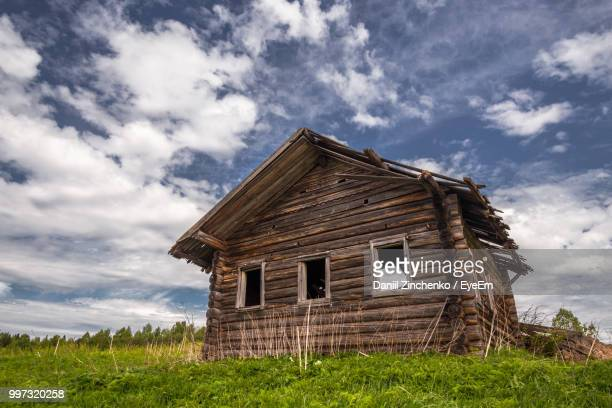 Low Angle View Of Abandoned House On Field Against Sky