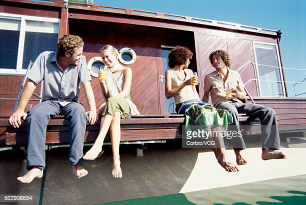 low angle view of adults hanging out on a boat - houseboat stock pictures, royalty-free photos & images
