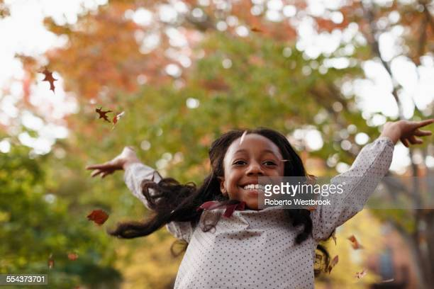 Low angle view of African American girl playing in autumn leaves