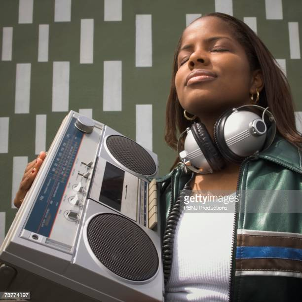 Low angle view of African woman listening to music on portable stereo