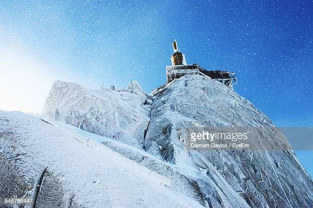 low angle view of aiguille du midi in snow against blue sky - aiguille de midi stock photos and pictures
