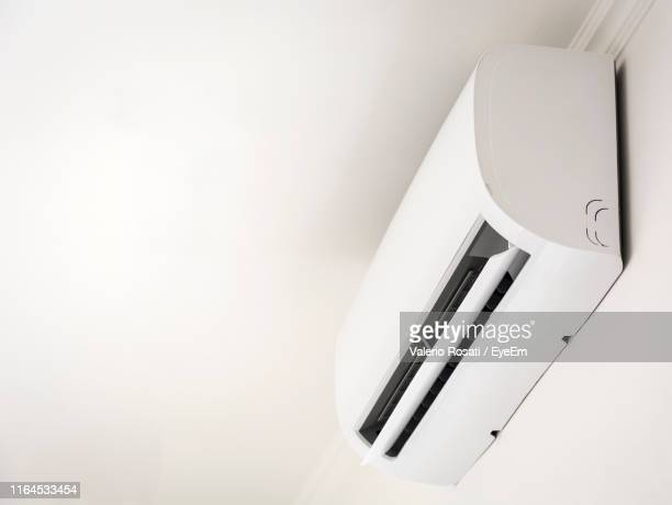 low angle view of air conditioner on wall - エアコン ストックフォトと画像
