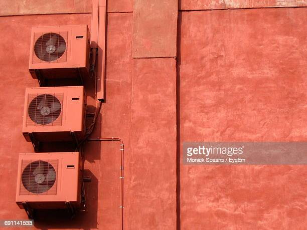 Low Angle View Of Air Conditioners On Brown Wall