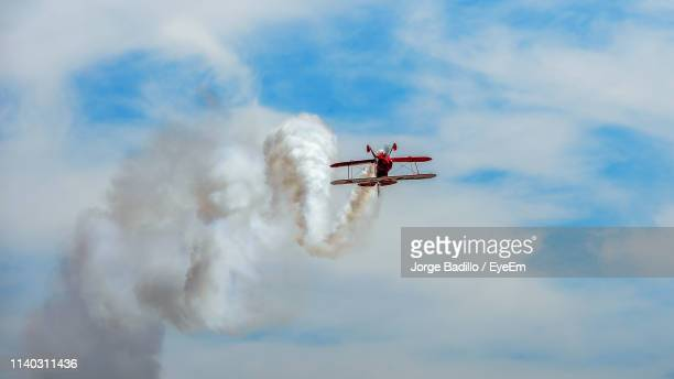 low angle view of air vehicle flying against cloudy sky - low flying aircraft stock pictures, royalty-free photos & images