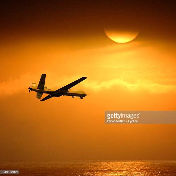 low angle view of air vehicle over sea against orange sky during sunset - steve matten stock pictures, royalty-free photos & images