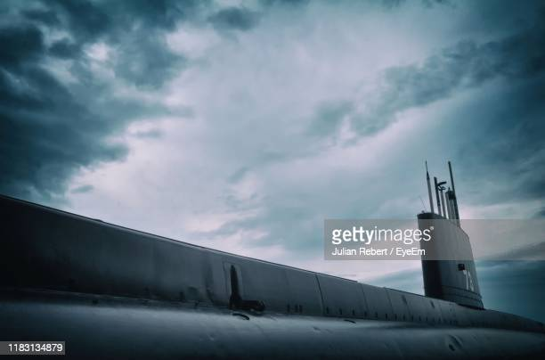 low angle view of airplane against cloudy sky - submarine stock pictures, royalty-free photos & images
