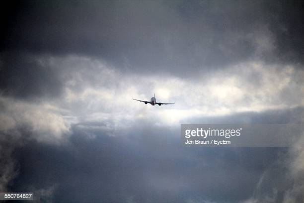 Low Angle View Of Airplane Against Cloudy Sky