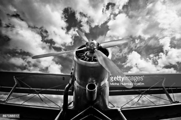 low angle view of airplane against cloudy sky - propeller stock pictures, royalty-free photos & images