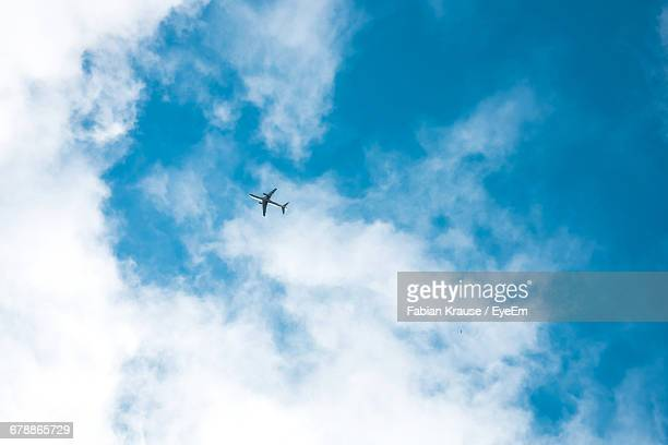 low angle view of airplane against the sky - airplane sky stock pictures, royalty-free photos & images