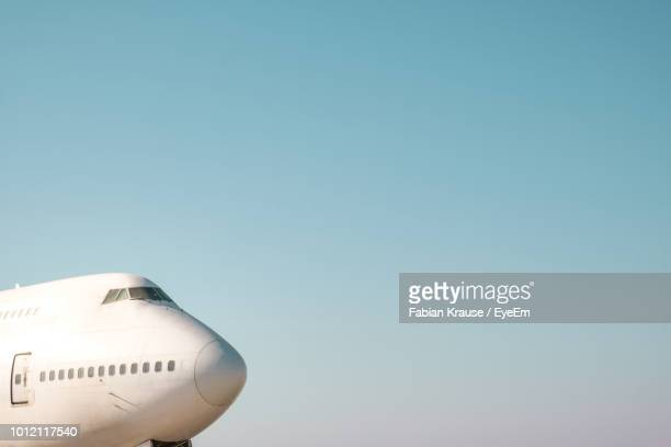 Low Angle View Of Airplane At Airport Against Clear Blue Sky