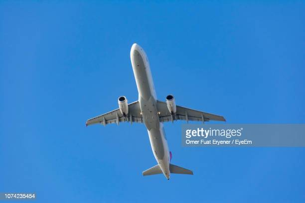 low angle view of airplane flying against blue sky - low flying aircraft stock pictures, royalty-free photos & images
