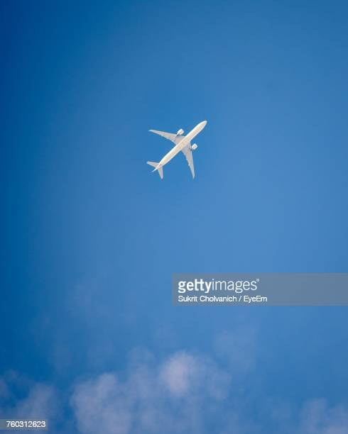 low angle view of airplane flying against blue sky - airplane sky stock pictures, royalty-free photos & images