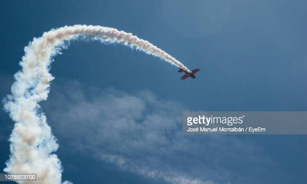 low angle view of airplane flying against clear blue sky - track imprint stock photos and pictures