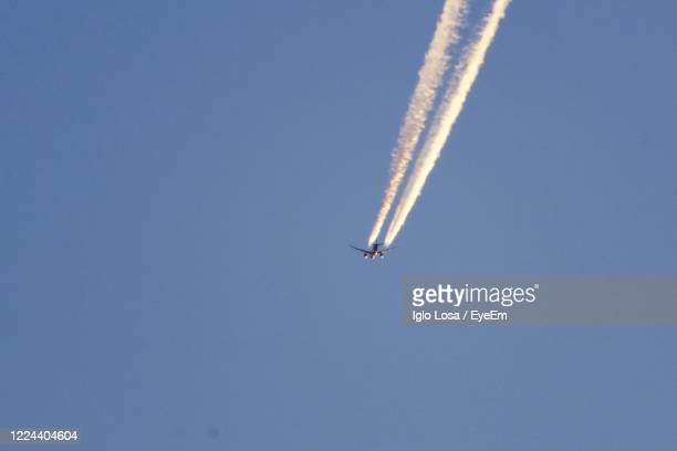 low angle view of airplane flying against clear blue sky - low flying aircraft stock pictures, royalty-free photos & images