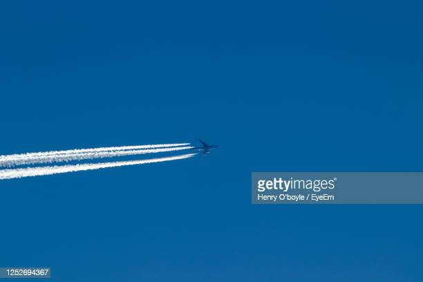 low angle view of airplane flying against clear blue sky - brixton stock pictures, royalty-free photos & images